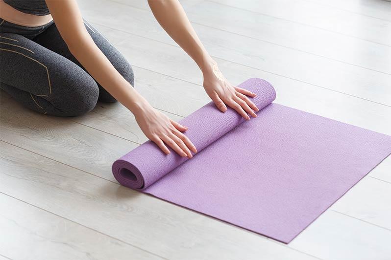 lady rolling yoga mat