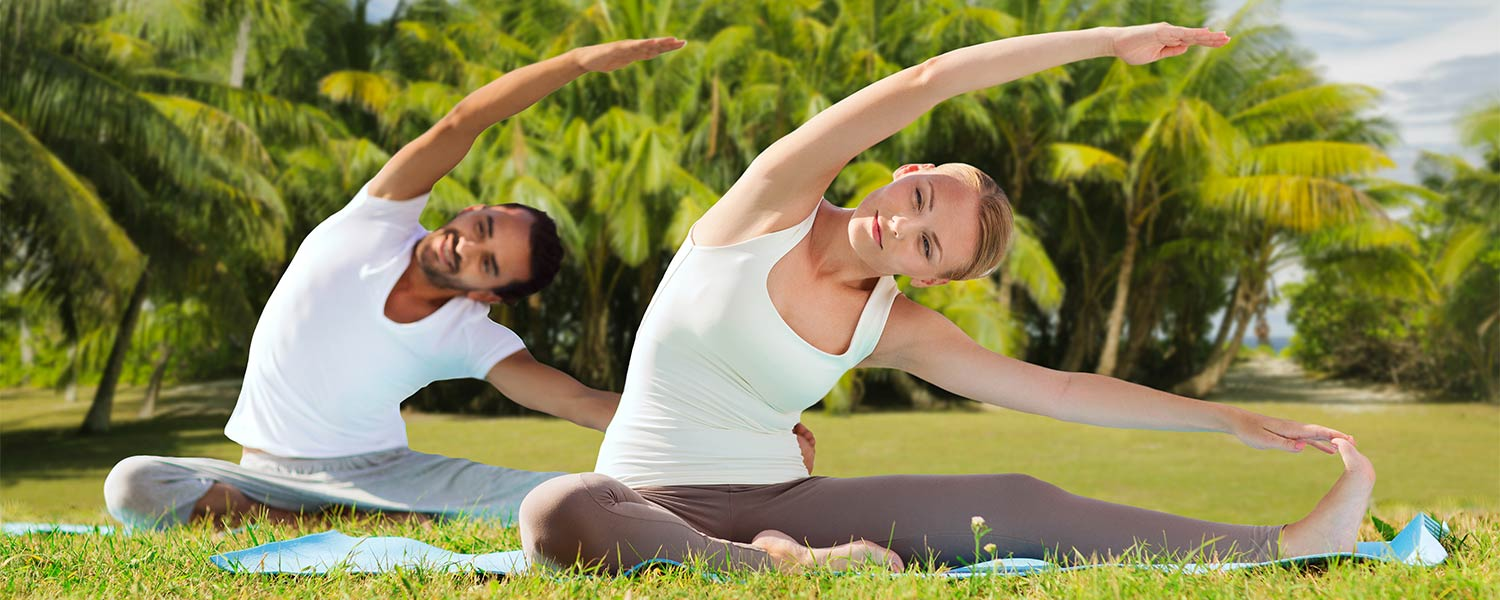 Man Woman doing yoga in tropical setting